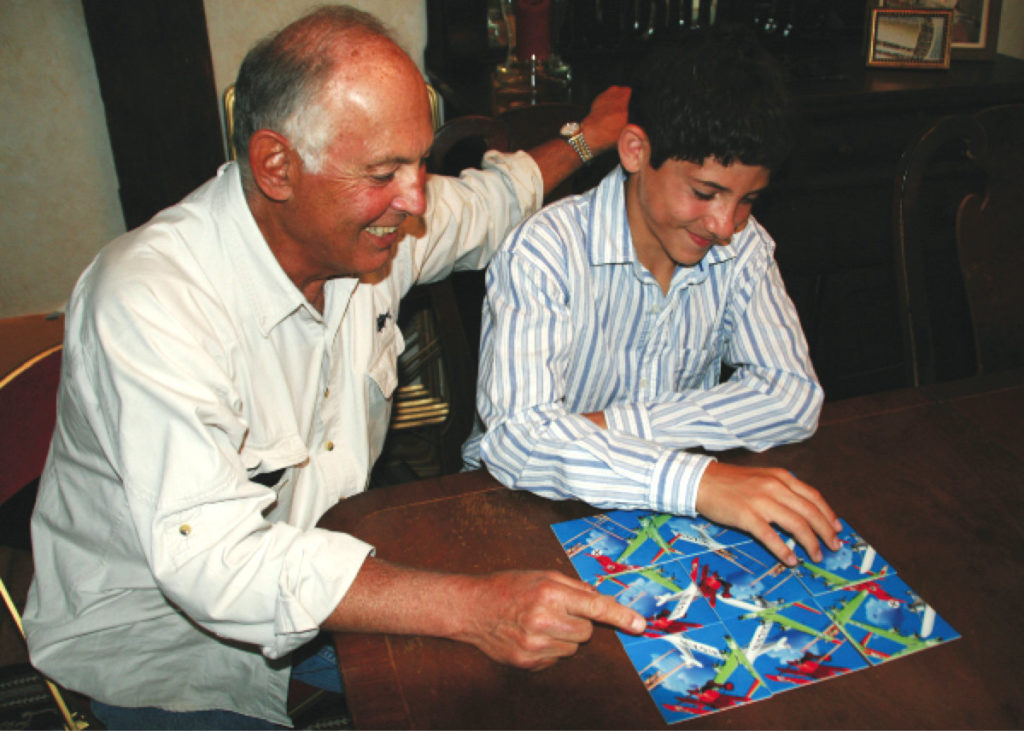 A grandfather and grandson bonding over a Scramble Squares® puzzle.